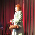 Judith Hibbert on stage in coat